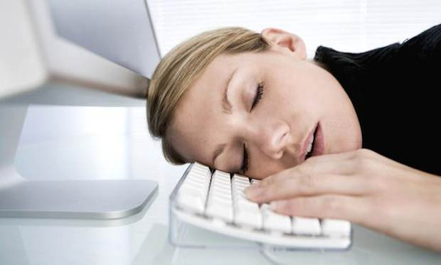 woman suffering from chronic fatigue sydrome asleep at the keypad