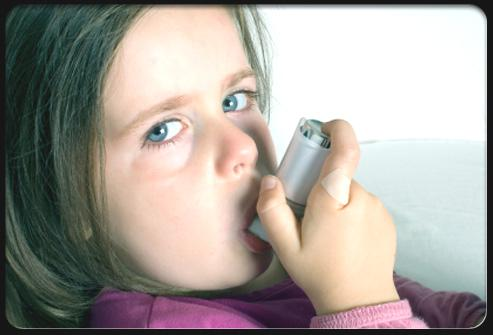 Girl with asthma sucking on inhaler