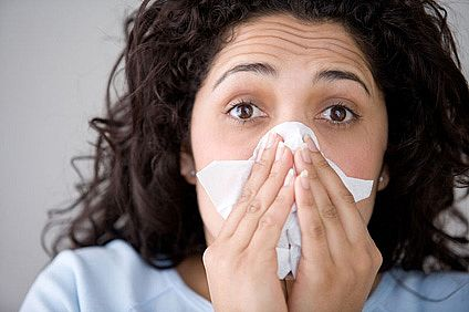 Woman with flu symptoms blowing her nose