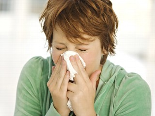 woman with common cold blows nose