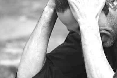 depressed man with hands on head looking downwards