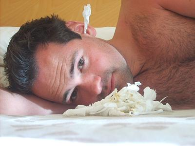 man lying down with ear infecton with paper plug in ear