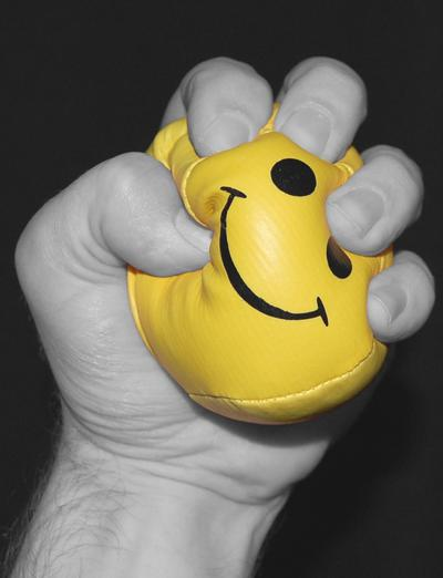 hand clenching and stressing a yellow happy face