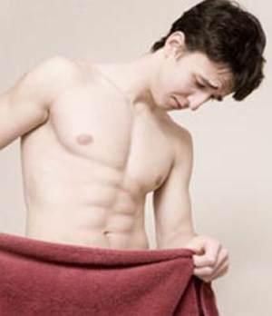 Man looking down behind towel at Genital Warts